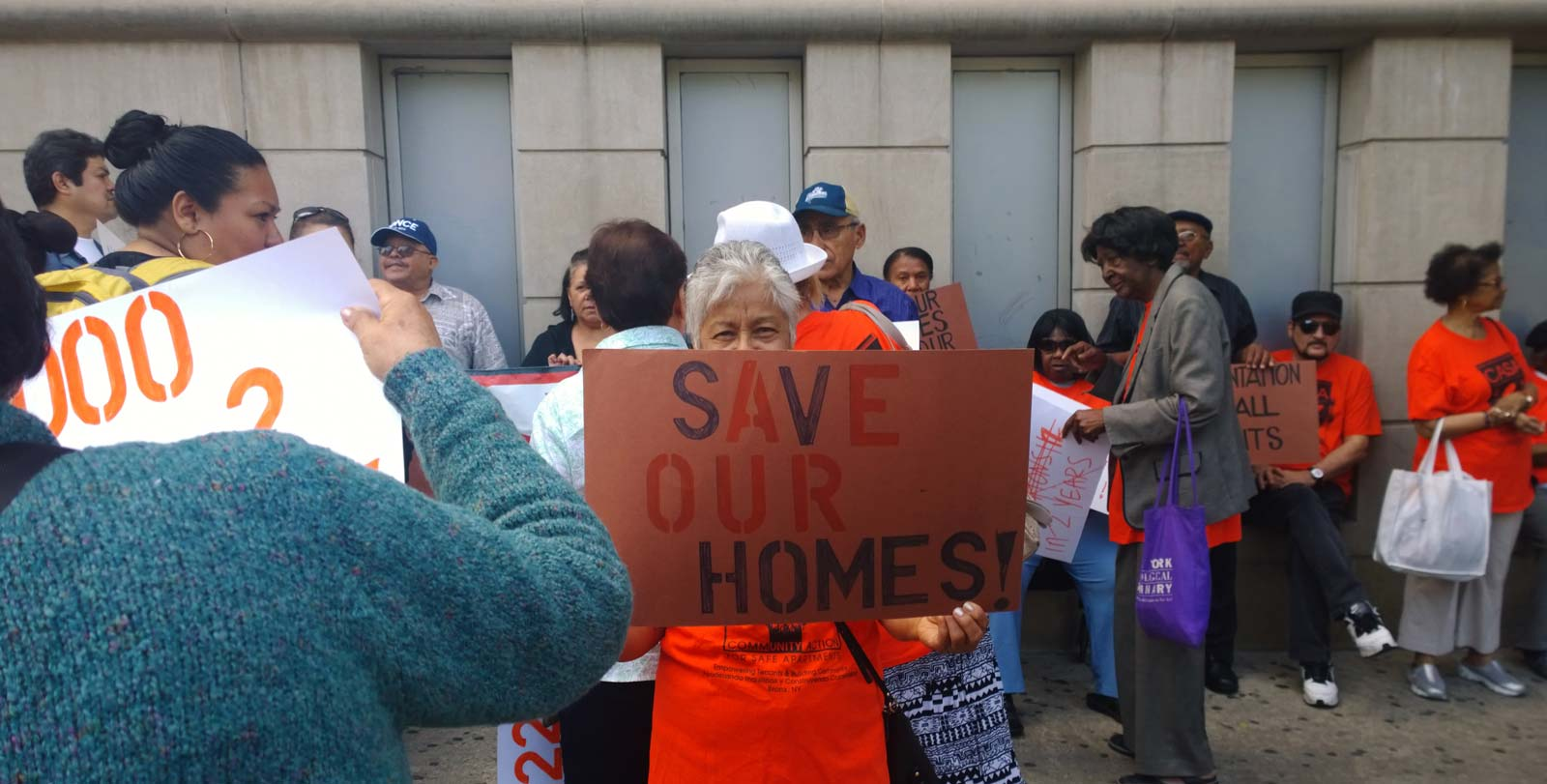 A group of Right to Counsel activists meet. One holds a sign reading Save Our Homes